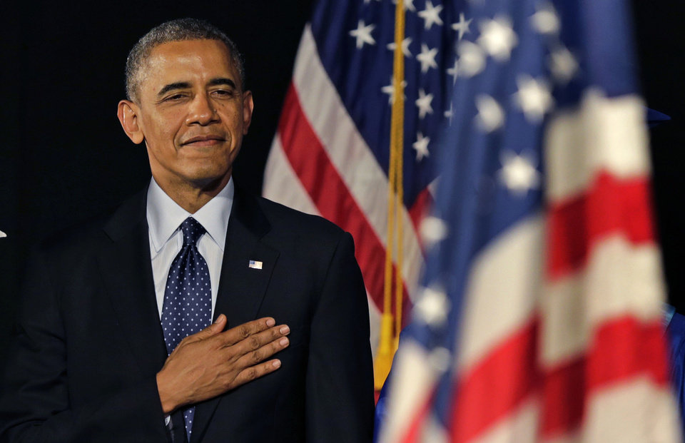Photo - President Obama stands for the National Anthem during the graduation ceremony for Worcester Technical High School, Wednesday, June 11, 2014, in Worcester, Mass. Afterward he will attend a democratic fundraiser in Massachusetts, before returning to Washington. (AP Photo/Charles Krupa)