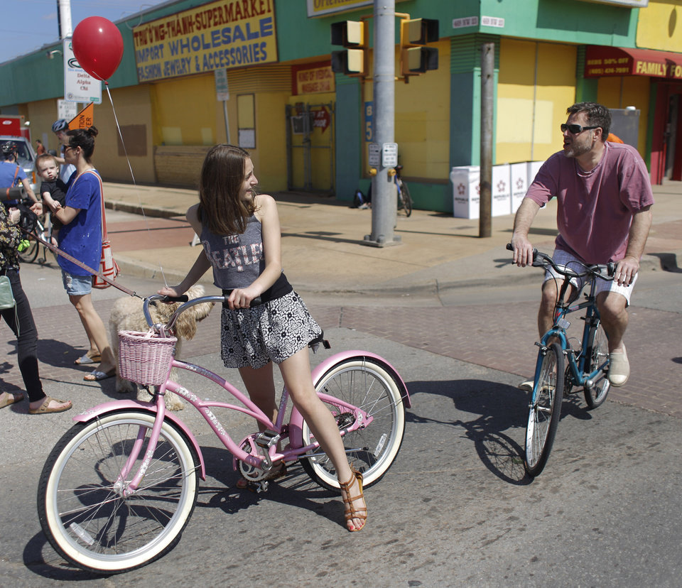 Photo - Bella McCray, 12, and her dad Kevin McCray ride their bikes  at Open Streets OKC, along NW 23rd Street between Robinson and Western, Sunday, March 22, 2015. Photo by Doug Hoke, The Oklahoman
