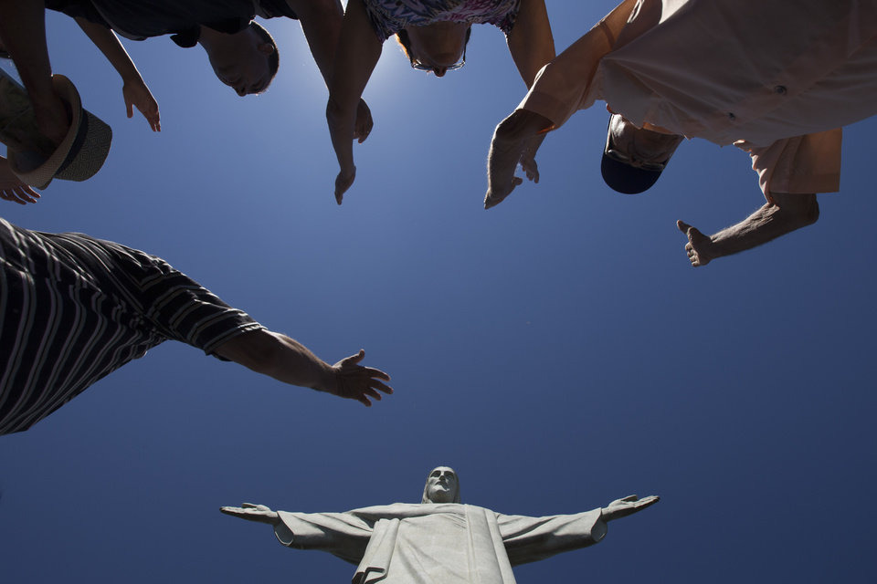 Photo - Visitors raise their arms to pray below the Christ Redeemer statue in Rio de Janeiro, Brazil, Tuesday, Jan. 21, 2014. Rio de Janeiro's famed Christ statue is being repaired after two fingers and its head were chipped during recent lightning storms. (AP Photo/Felipe Dana)
