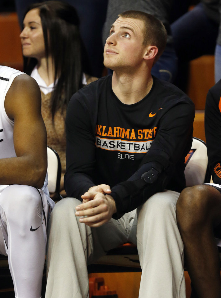 Photo - An injured Phil Forte (13) sits on the OSU bench during a men's college basketball game between Oklahoma State and Missouri State at Gallagher-Iba Arena in Stillwater, Okla., Saturday, Dec. 5, 2015. Missouri State won 64-63. Photo by Nate Billings, The Oklahoman
