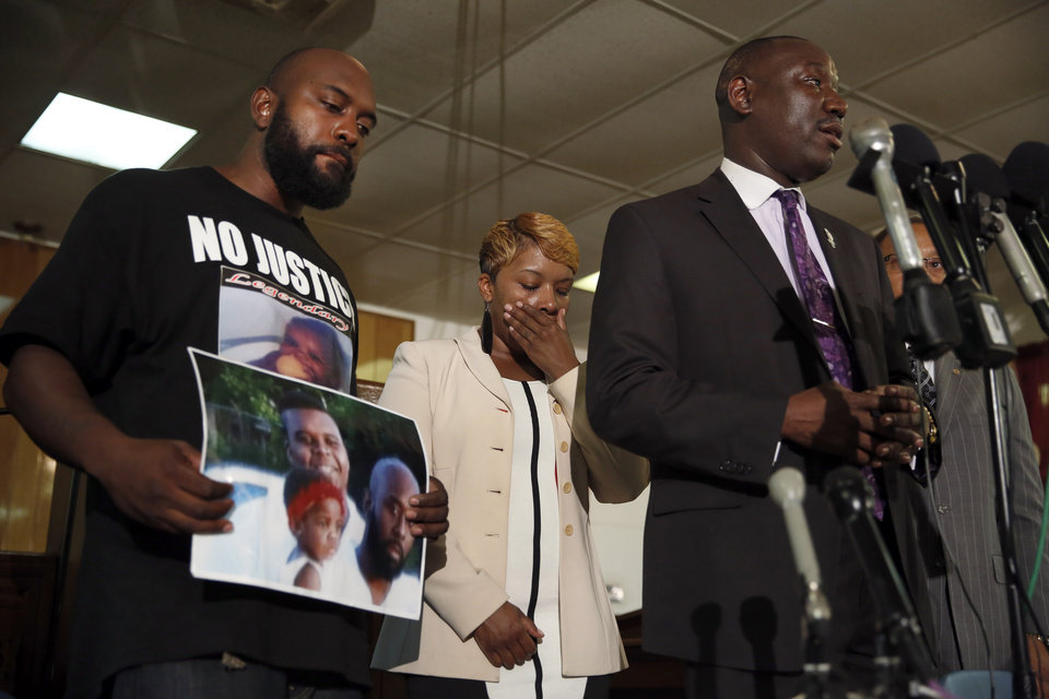 Photo - Lesley McSpadden, center, and Michael Brown Sr., left, the parents of Michael Brown, listen as attorney Benjamin Crump speaks during a news conference Monday, Aug. 11, 2014, in Jennings, Mo. Michael Brown, 18, was shot and killed in a confrontation with police in the St. Louis suburb of Ferguson, Mo, on Saturday, Aug. 9, 2014. (AP Photo/Jeff Roberson)