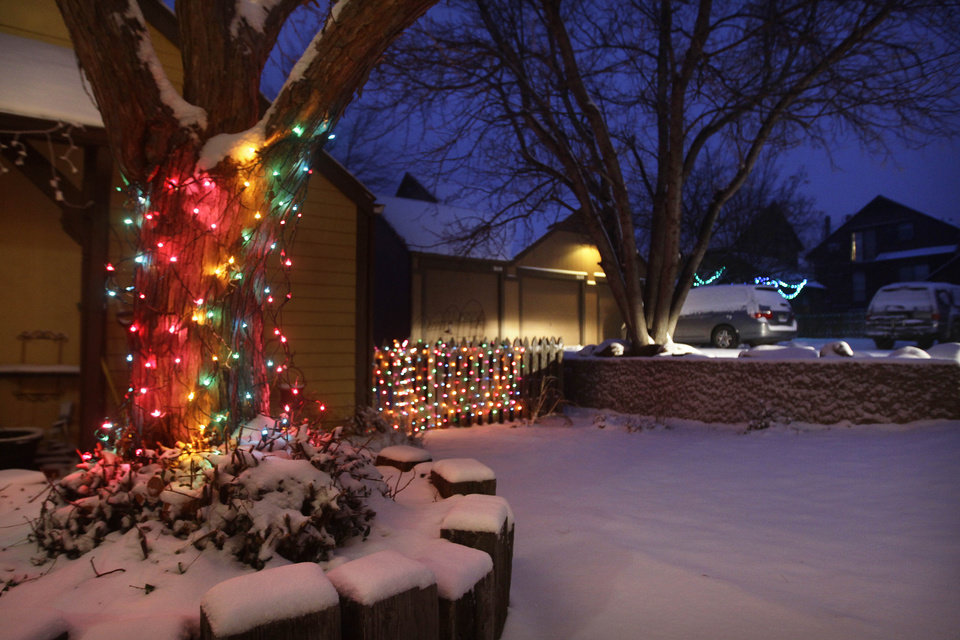 Christmas lights hang from a tree and a fence dusted with new snow, as the pre-dawn sky glows blue, in Boulder, Colo., Wednesday Dec. 19, 2012. A storm that has dumped more than a foot of snow in the Rocky Mountains is heading east and is forecast to bring the first major winter storm of the season to the central plains and Midwest. (AP Photo/Brennan Linsley)