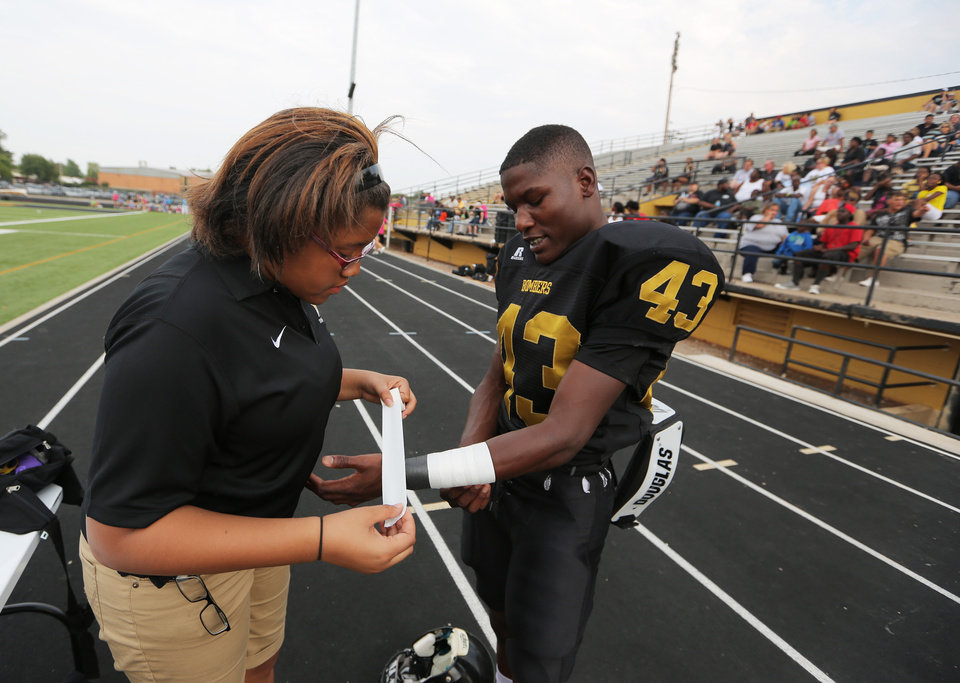 Photo - Ashley Hopkins tapes Tarez Easley's wrists before a junior varsity scrimmage between Midwest City and Carl Albert at Bomber Stadium in Midwest City, Thursday, Aug. 23, 2012.  Photo by Garett Fisbeck, For The Oklahoman