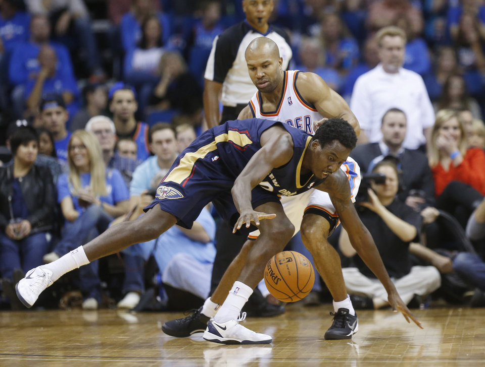 New Orleans Pelicans forward Al-Farouq Aminu (0) reaches for the ball in front of Oklahoma City Thunder guard Derek Fisher in the third quarter of an NBA basketball preseason game in Tulsa, Okla., Thursday, Oct. 17, 2013. New Orleans won 105-102. (AP Photo/Sue Ogrocki) ORG XMIT: OKSO117