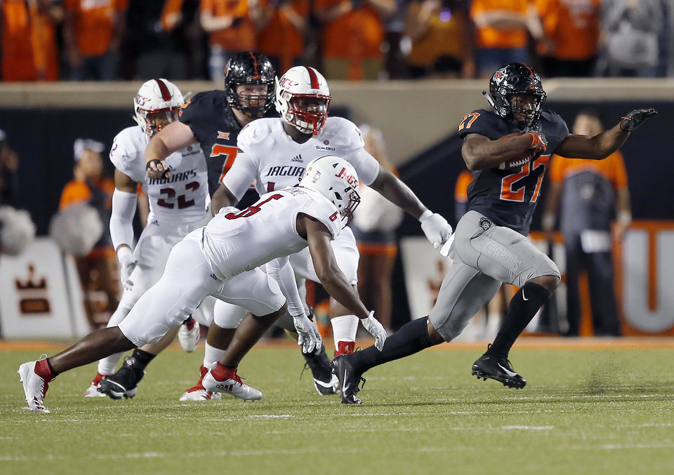 Photo - Oklahoma State's J.D. King (27) gets by South Alabama's Nigel Lawrence (6) during a college football game between Oklahoma State (OSU) and South Alabama at Boone Pickens Stadium in Stillwater, Okla., Saturday, Sept. 8, 2018. Photo by Sarah Phipps, The Oklahoman