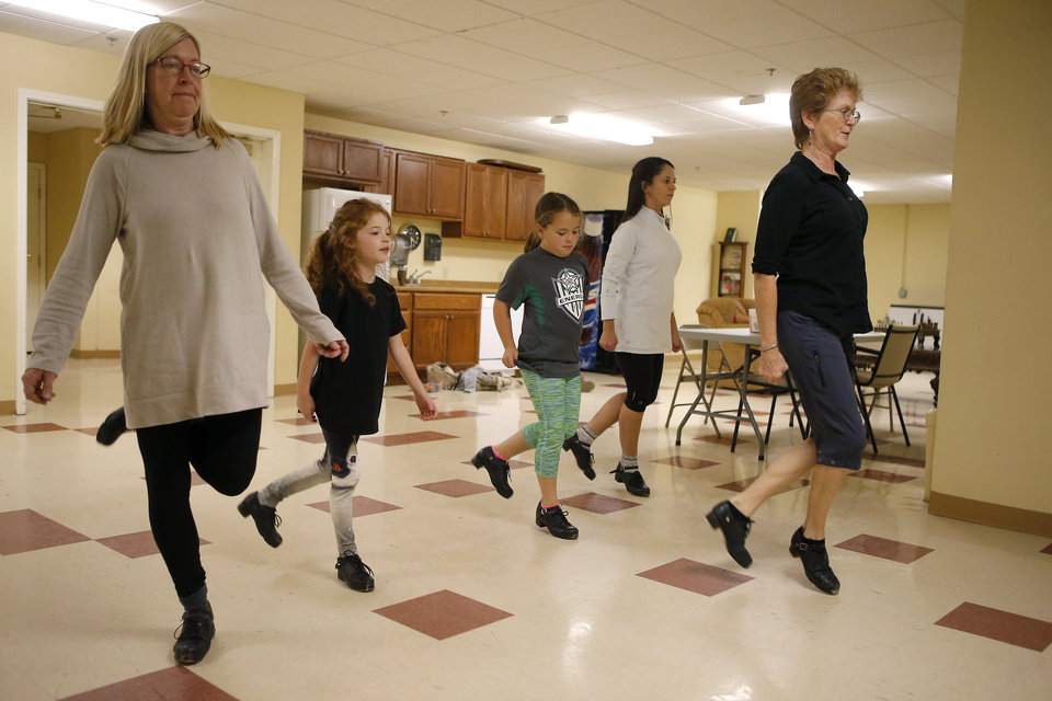 Photo -  Jean Hill, right, works with Andrea Crouch, left, and her daughter, Sophie Crouch, 7, along with Morgan Mitchell, 8, and her mother, Keri Mitchell, during an Irish dance class held at Touchmark Retirement Community in Edmond. [Photo by Bryan Terry, The Oklahoman]