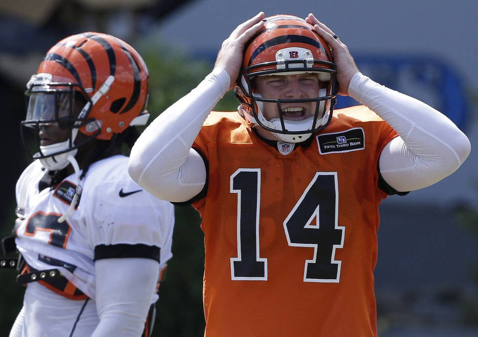 Photo - Cincinnati Bengals quarterback Andy Dalton (14) calls an audible during practice at the NFL football team's training camp on Sunday, July 28, 2013, in Cincinnati. Running back BenJarvus Green-Ellis, left, looks on. (AP Photo/Al Behrman)