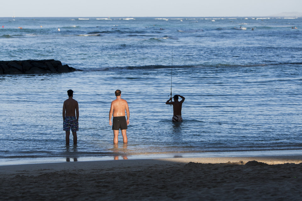 Photo - Beach goers are seen on Waikiki Beach, Thursday, Aug. 7, 2014, in Honolulu.  Hawaii is bracing for both Hurricane Iselle and Julio which are on course to hit the Hawaiian Islands.  (AP Photo/Marco Garcia)
