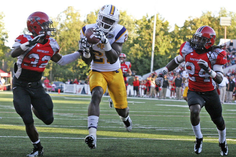 Photo -   In this photo taken Sept. 22, 2012 and provided by Tennessee Tech University, Tech wide receiver Da'Rick Rogers (21) scores a touchdown between Southeast Missouri State defenders Josh Coleman (32) and Kweku Arkorful (24) during a college football game in Cape Girardeau, Mo. One year ago, Rogers was an all-Southeastern Conference receiver performing in one of college football's largest stadiums. Now the former Tennessee star plays in front of fewer than 10,000 fans at Tennessee Tech. (AP Photo/Tennessee Tech University)