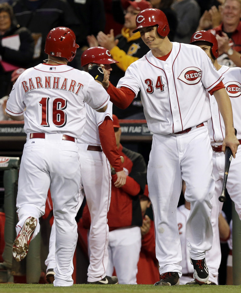 Photo - Cincinnati Reds' Tucker Barnhart (16) is congratulated by Homer Bailey (34) after Barnhart hit a solo home run off Milwaukee Brewers starting pitcher Marco Estrada in the fifth inning of a baseball game, Thursday, May 1, 2014, in Cincinnati. (AP Photo/Al Behrman)