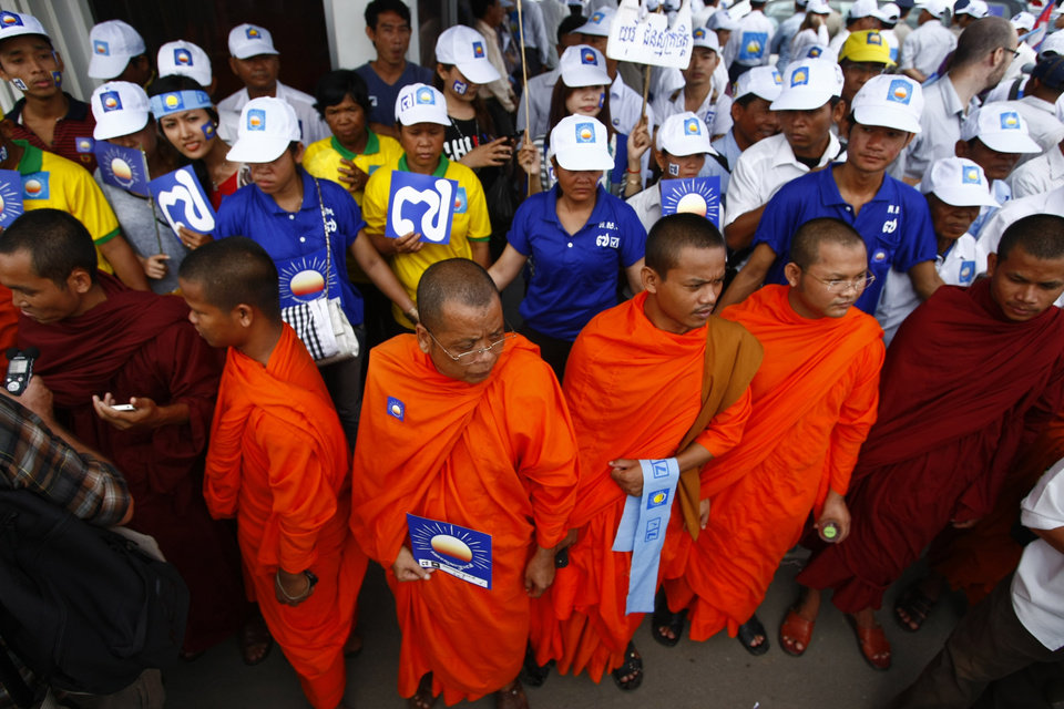 Photo - Cambodian Buddhist monks join supporters of the Cambodia National Rescue Party (CNRP) as they wait for Sam Rainsy's arrival outside the Phnom Penh International Airport in Phnom Penh, Cambodia, Friday, July 19, 2013. Thousands of cheering supporters greeted Cambodian opposition leader Sam Rainsy as he returned from self-imposed exile Friday to spearhead his party's election campaign against well-entrenched Prime Minister Hun Sen. (AP Photo/Heng Sinith)