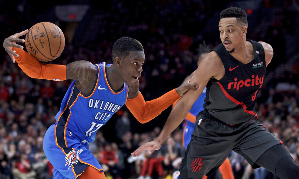 Photo - Oklahoma City Thunder guard Dennis Schroeder, left, loses the ball while dribbling next to Portland Trail Blazers guard CJ McCollum during the first half of an NBA basketball game in Portland, Ore., Thursday, March 7, 2019. (AP Photo/Craig Mitchelldyer)