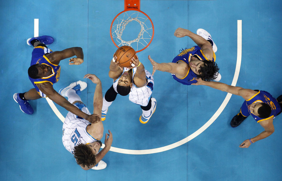 Photo - New Orleans Hornets forward Anthony Davis (23) dunks between Golden State Warriors center Andrew Bogut, second right, guard Stephen Curry, right, forward Harrison Barnes, left, and Hornets center Robin Lopez (15) in the first half of an NBA basketball game in New Orleans, Monday, March 18, 2013. (AP Photo/Gerald Herbert)