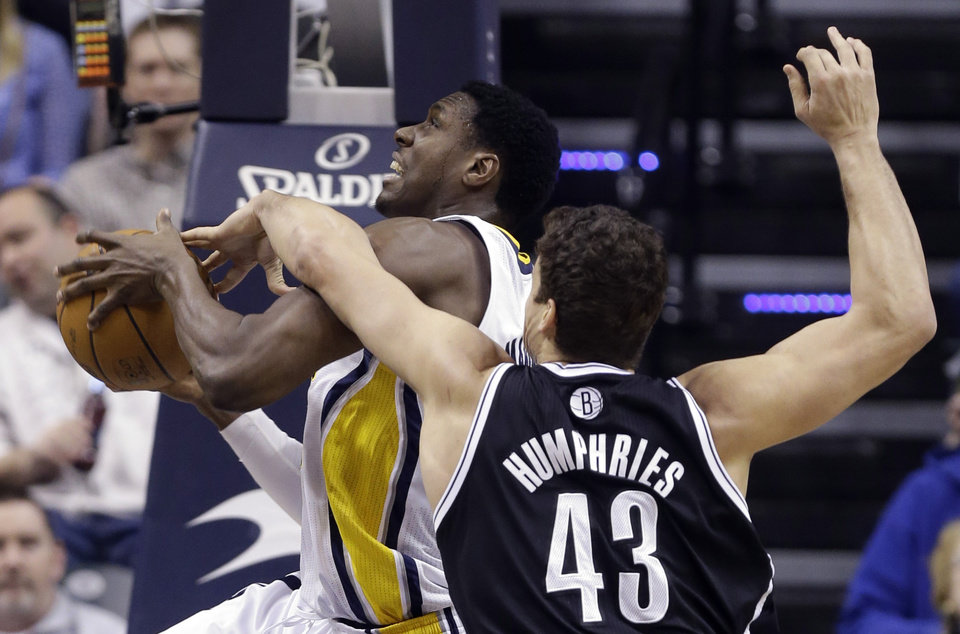 Indiana Pacers center Ian Mahinmi, left, is fouled by Brooklyn Nets forward Kris Humphries (43) as he shoots in the first half of an NBA basketball game in Indianapolis, Monday, Feb. 11, 2013. (AP Photo/Michael Conroy)