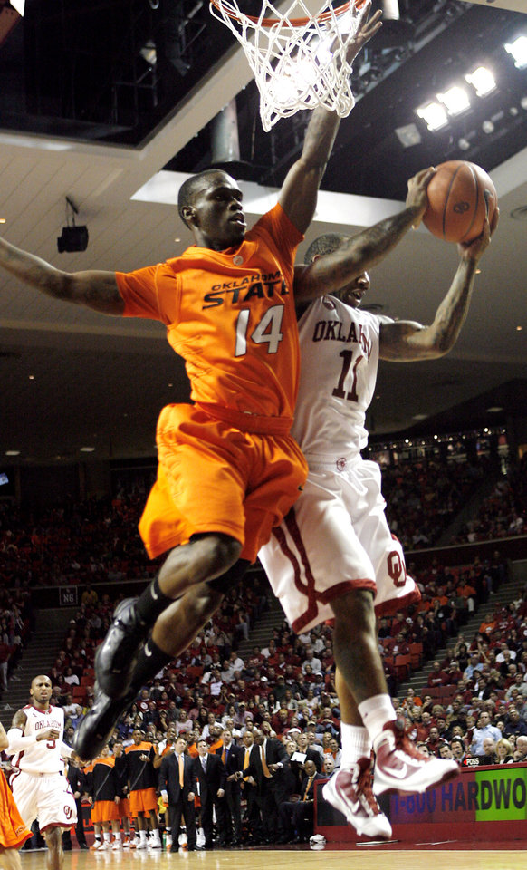 Photo - OSU's Ray Penn (14) and OU's Tommy Mason-Griffin (14) battle for a rebound during the first half of the college bedlam basketball game between The University of Oklahoma Sooners (OU) and Oklahoma State University University Cowboys (OSU) at the Lloyd Noble Center on Monday, Jan. 11, 2010, in Norman, Okla.