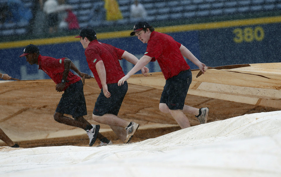 Photo - Atlanta Braves grounds  crew members work to cover the infield at Turner Field during a rain shower in the sixth inning of a baseball game against Philadelphia Phillies in Atlanta, Sunday, July 20, 2014. (AP Photo/John Bazemore)