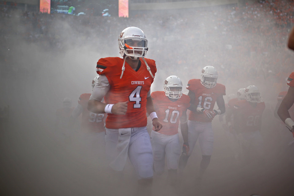 Photo - Oklahoma State's J.W. Walsh (4) runs out onto the field before a college football game between the Oklahoma State University Cowboys (OSU) and the Lamar University Cardinals at Boone Pickens Stadium in Stillwater, Okla., Saturday, Sept. 14, 2013. Photo by Sarah Phipps, The Oklahoman