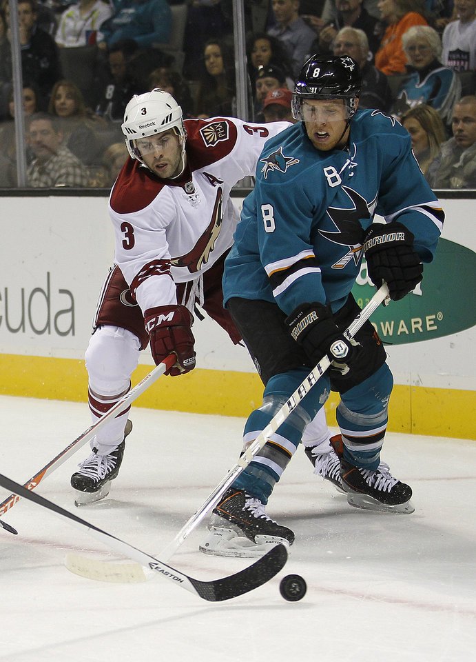 San Jose Sharks center Joe Pavelski (8) battles for the puck against Phoenix Coyotes defenseman Keith Yandle (3) during the first period an NHL hockey game in San Jose, Calif., Saturday, Oct. 5, 2013. (AP Photo/Tony Avelar)