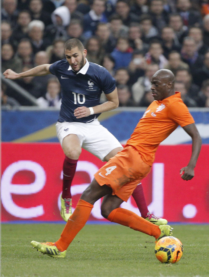 Photo - Karim Benzema of France, left, kicks the ball next Netherlands' Bruno Martins Indi during the international friendly match between France and Netherlands at the Stade de France stadium, outside Paris, Wednesday, March 5, 2014. (AP Photo/Christophe Ena)