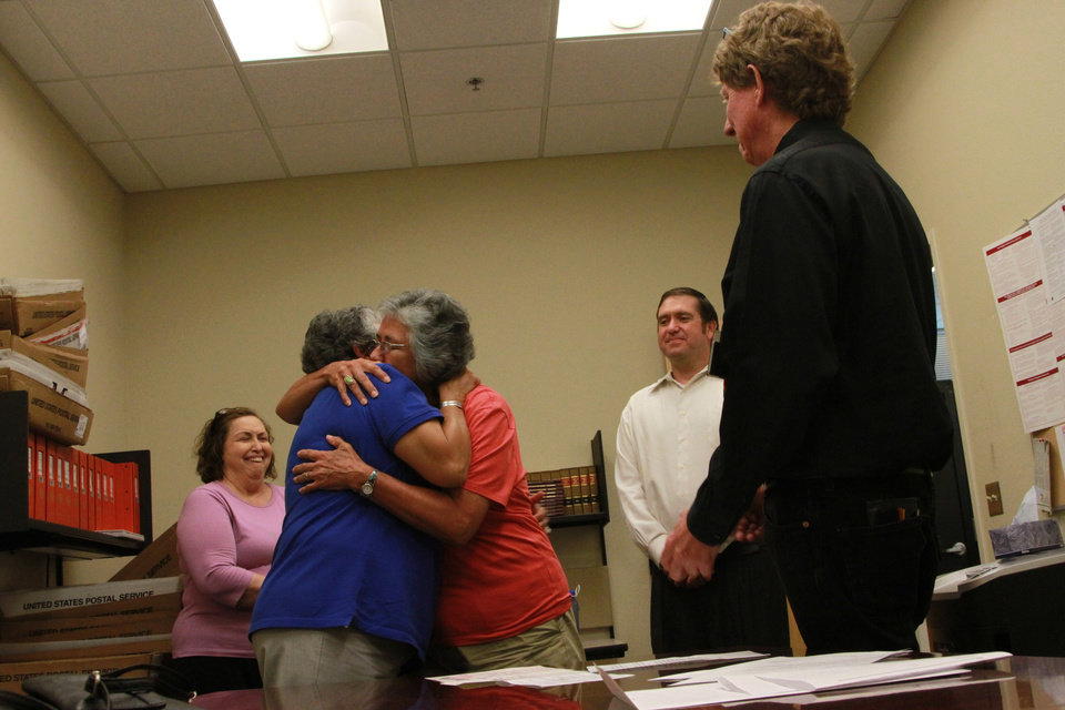 Photo - Catherine Martinez and Linda Montoya hug after Dona Ana County employee and  Reverend Jess C. Williams married them at the Dona Ana County Clerk's Office in Las Cruces, New Mexico, Wednesday, Aug. 21, 2013. More than 40 same-sex couples obtained their marriage licenses after the county clerk announced the county would be the first in New Mexico to marry same-sex couples. (AP Photo/Juan Carlos Llorca)
