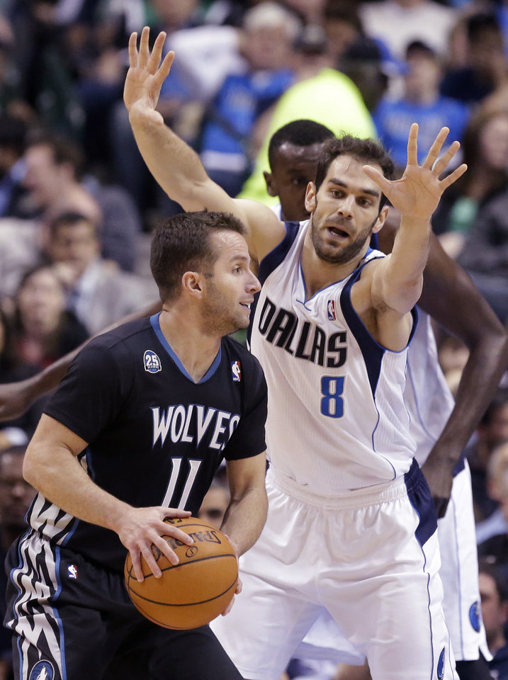 Photo - Minnesota Timberwolves guard J.J. Barea (11) looks to pass against Dallas Mavericks guard Jose Calderon (8) of Spain during the first half an NBA basketball game Wednesday, March 19, 2014, in Dallas. (AP Photo/LM Otero)