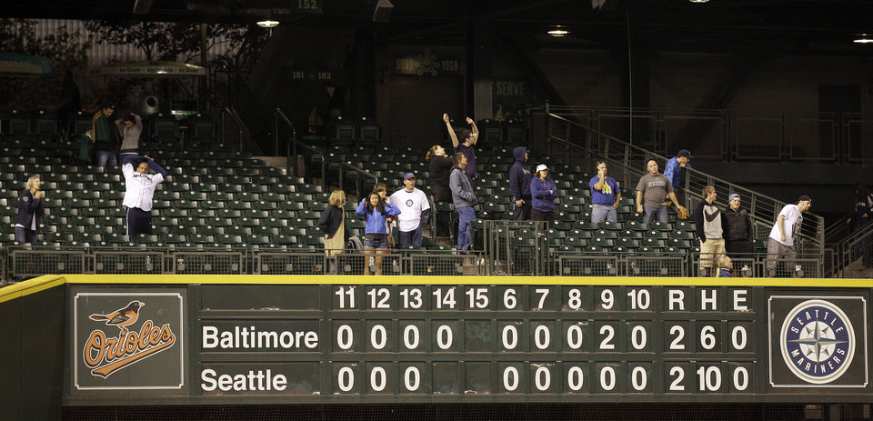 Photo -   Fans stretch during the 14th inning of a baseball game between Baltimore Orioles and the Seattle Mariners, Tuesday, Sept. 18, 2012, in Seattle. (AP Photo/Ted S. Warren)