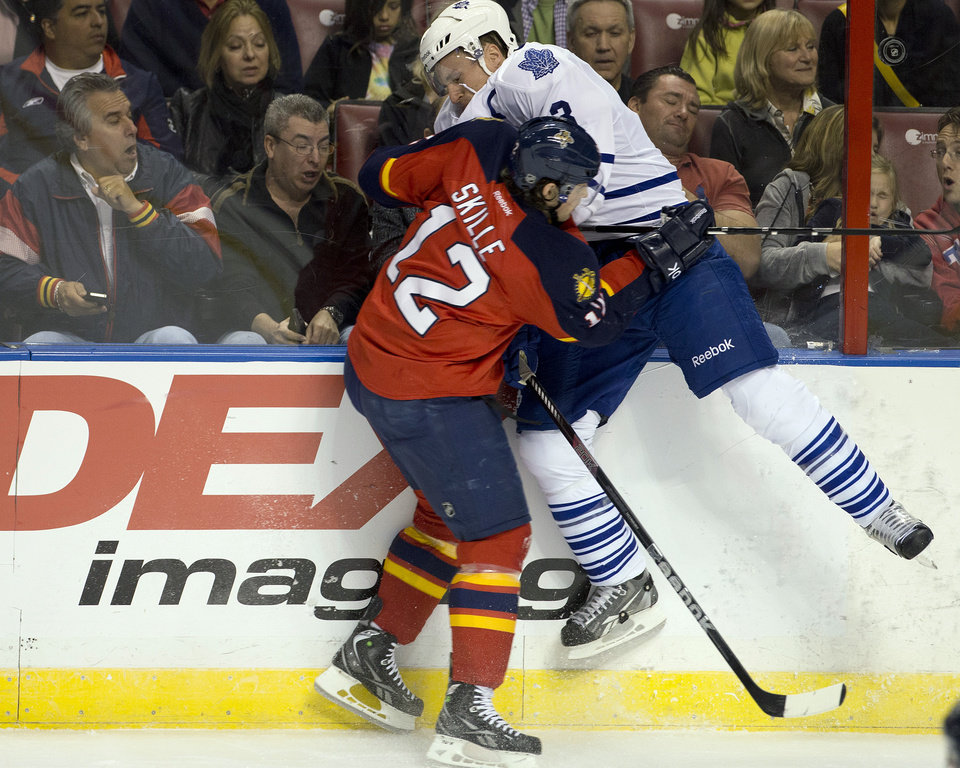 Photo - Fans react as Florida Panthers' Jack Skille (12) slams Toronto Maple Leafs' Dion Phaneuf (3) into the boards during the first period of an NHL hockey game in Sunrise, Fla., Monday, Feb. 18, 2013.  (AP Photo/J Pat Carter)