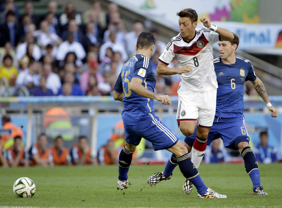 Photo - Germany's Mesut Ozil tries to get past his defenders Argentina's Martin Demichelis and Lucas Biglia (6) during the World Cup final soccer match between Germany and Argentina at the Maracana Stadium in Rio de Janeiro, Brazil, Sunday, July 13, 2014. (AP Photo/Felipe Dana)