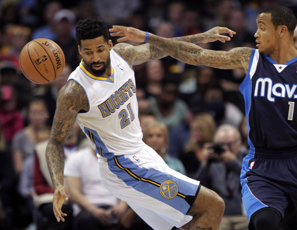 Photo - Denver Nuggets forward Wilson Chandler (21) lunges for a loose ball against Dallas Mavericks guard Monta Ellis (11) during the second quarter of an NBA basketball game in Denver on Saturday, Nov. 23, 2013. (AP Photo/Joe Mahoney)