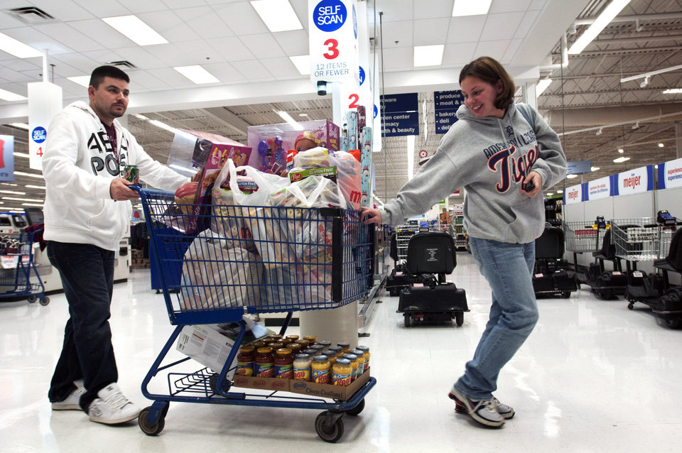 Photo -   Jeremy and Rebecca Wheeler guide their full cart out of a Meijer, in Grand Rapids, Mich., shortly after the store's 6AM sale began on Thanksgiving Day, Thursday, Nov. 22, 2012. Her mother, Pat Brakla, checks out behind her. Stores typically open in the wee hours of the morning on the day after Thanksgiving known as Black Friday, named for the period when stores traditionally turn a profit for the year. But Black Friday openings have crept earlier and earlier over the past few years. Now, stores from Wal-Mart to Toys R Us are opening their doors on Thanksgiving evening, hoping Americans will be willing to shop soon after they finish their pumpkin pie.(AP Photo/The Grand Rapids Press, Chris Clark ) ALL LOCAL TV OUT; LOCAL TV INTERNET OUT