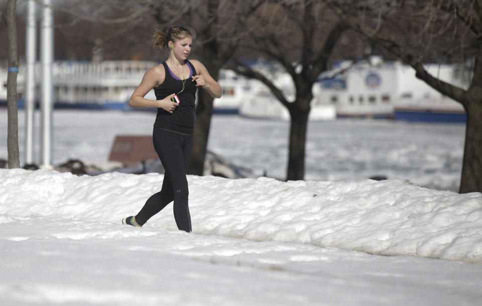 Photo - A runner runs along the lake shore Wednesday, Feb. 19, 2014, in Chicago. Weeks of subfreezing weather are giving way, at least briefly, to temperatures in the 50s, putting cities on guard for flooding, roof collapses and clogged storm drains. (AP Photo/Kiichiro Sato)