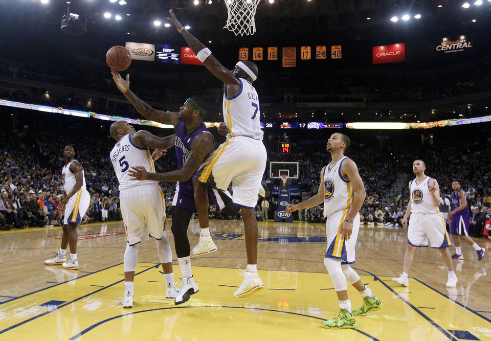 Photo - Sacramento Kings center DeMarcus Cousins tries to shoot between Golden State Warriors' Marreese Speights (5) and Jermaine O'Neal (7) during the first half of an NBA basketball game Friday, April 4, 2014, in Oakland, Calif. (AP Photo/Marcio Jose Sanchez)