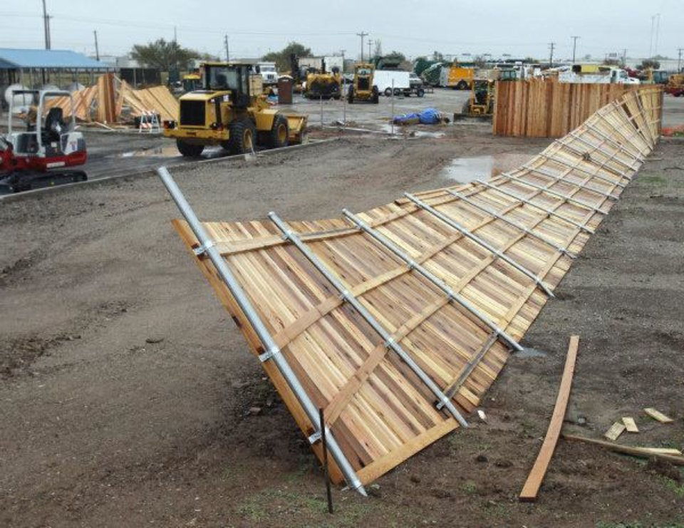 Photo - A new wood fence at the City of Norman's CNG station near Max Westheimer Airport lies on its side on Tuesday in Norman. The fence was blown over during Monday nights severe weather.  STEVE SISNEY - THE OKLAHOMAN