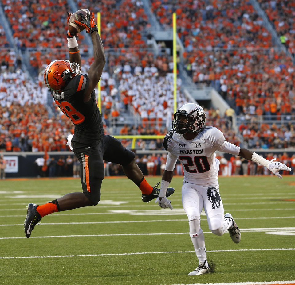 Photo - Oklahoma State's James Washington (28) catches a touchdown pass over Texas Tech's Tevin Madison (20) during a college football game between the Oklahoma State Cowboys (OSU) and the Texas Tech Red Raiders at Boone Pickens Stadium in Stillwater, Okla., Thursday, Sept. 25, 2014. Photo by Bryan Terry, The Oklahoman