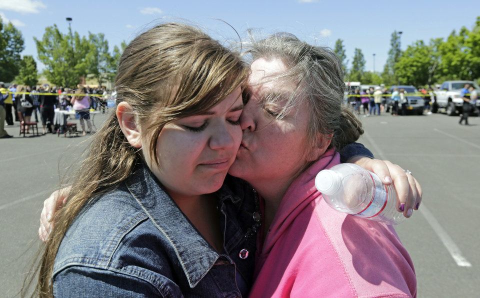 Photo - Freshman Britani Iuliano, 15, embraces her mother Wendi Iuliano after students arrived at shopping center parking lot in Wood Village, Ore., after a shooting at Reynolds High School Tuesday, June 10, 2014, in nearby Troutdale. A gunman killed a student at the high school east of Portland Tuesday and the shooter is also dead, police said. (AP Photo/Rick Bowmer)