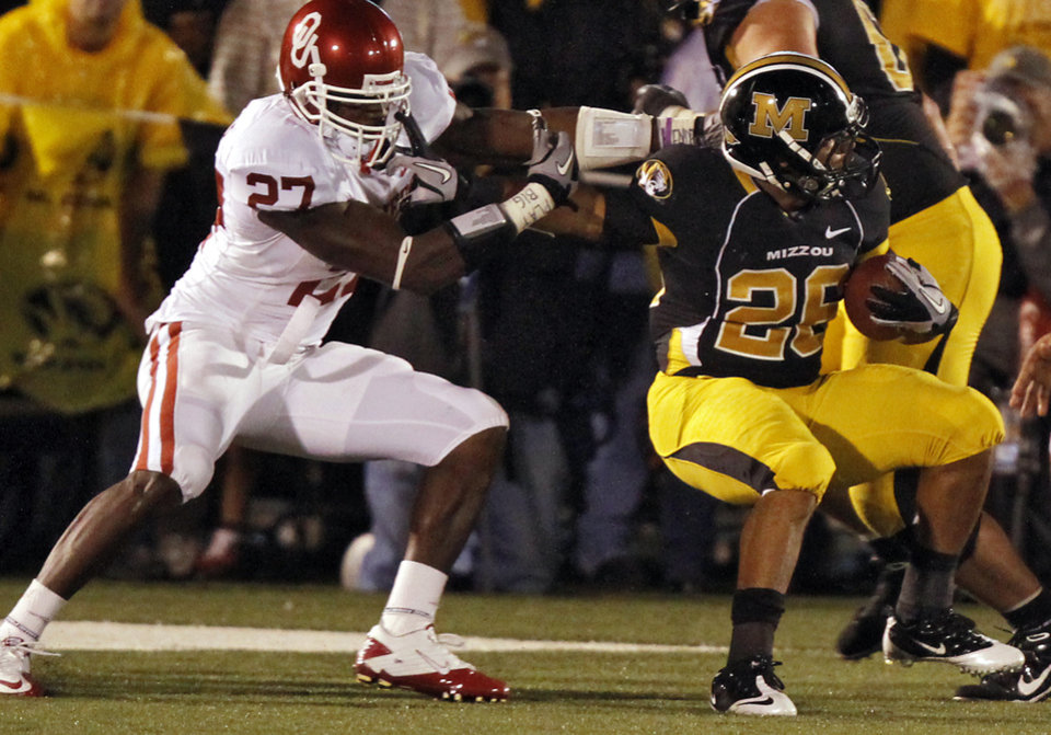 Photo - Oklahoma's Sam Proctor (27) tries to stop Missouri's De'Vion Moore (26) during the second half of the college football game between the University of Oklahoma Sooners (OU) and the University of Missouri Tigers (MU) on Saturday, Oct. 23, 2010, in Columbia, Mo. Oklahoma lost the game 36-27. Photo by Chris Landsberger, The Oklahoman