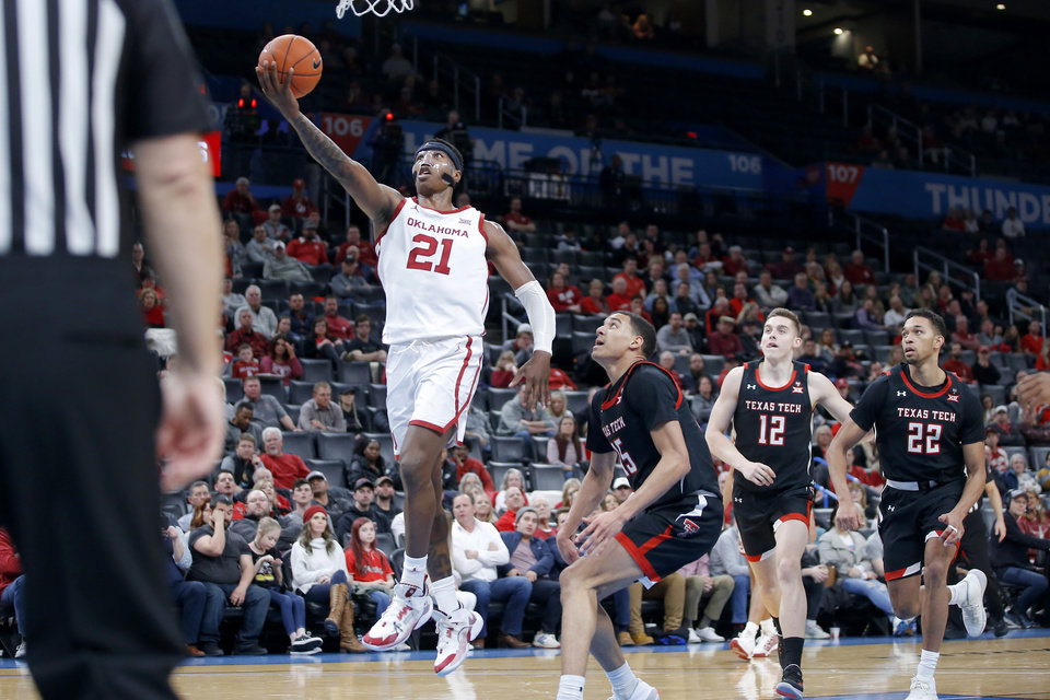 Photo - Oklahoma's Kristian Doolittle (21) goes to the basket past Texas Tech's Kevin McCullar (15), Andrei Savrasov (12) and TJ Holyfield (22) during a men's NCAA college basketball game between the University of Oklahoma Sooners (OU) and the Texas Tech Red Raiders at Chesapeake Energy Arena in Oklahoma City, Tuesday, Feb. 25, 2020. Oklahoma won 65-51. [Bryan Terry/The Oklahoman]