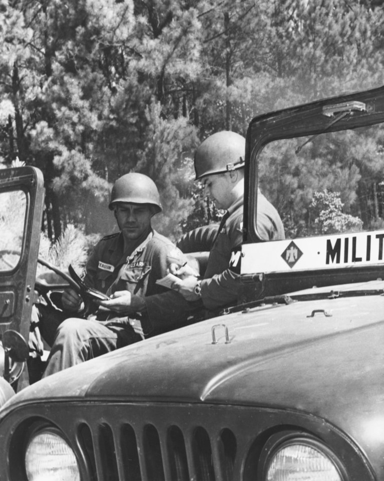 Photo - Sp4 Bettis demonstrates how some Thunderbirds would reap trouble from disobeying speed laws.  The move was made to prevent accidents on range roads during Thunderbird arms qualification at summer camp.  Staff photographer unknown.  Staff photo dated 07/21/1962 and published on 07/26/1962 in The Oklahoma City Times.