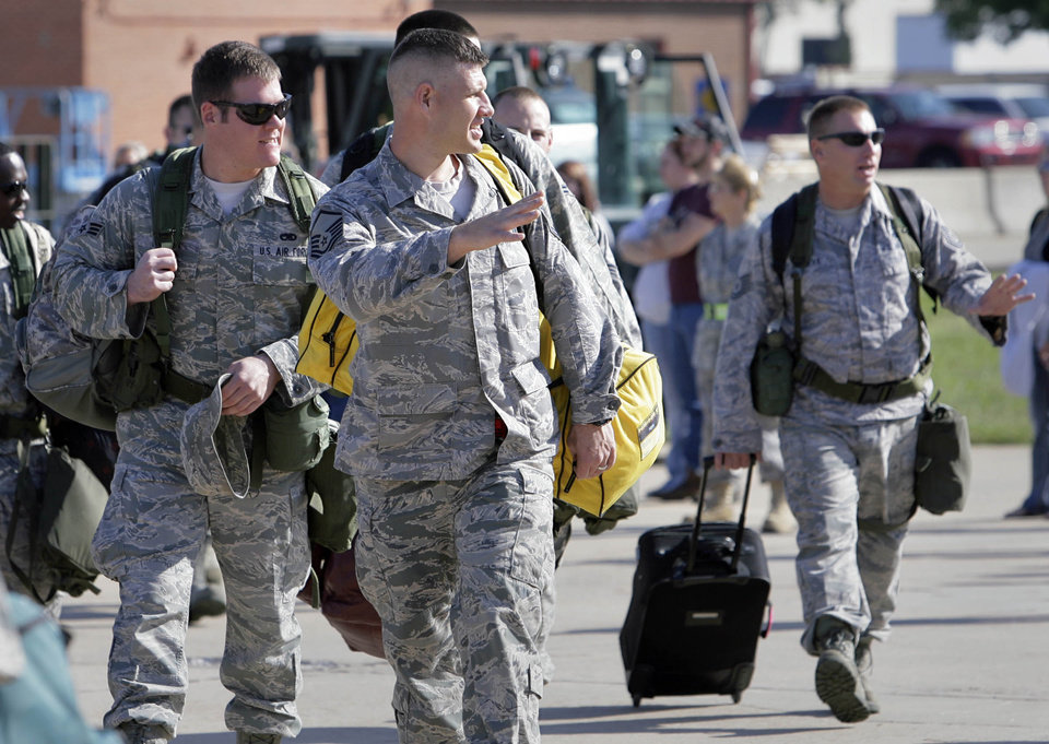 MILITARY DEPLOYMENT: Members of 138th Fighter Wing of the Oklahoma Air National Guard wave to their famiies as they walk from a staging hanger to the plane for deployment from Tulsa, OK Sept. 28, 2011, to Iraq to help support the drawn down of forces. MICHAEL WYKE/Tulsa World