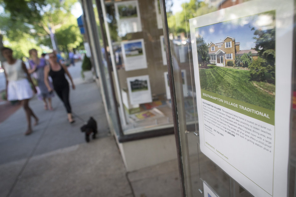 Photo - In this photo taken on Friday, July 11, 2014, pedestrians pass a real estate sales office displaying listings that exceed $1 million in Southampton, N.Y. Studies show the gap separating the rich from the working poor has been ever-widening in recent years and few places provide that evidence as starkly as Long Island's Hamptons. (AP Photo/John Minchillo)