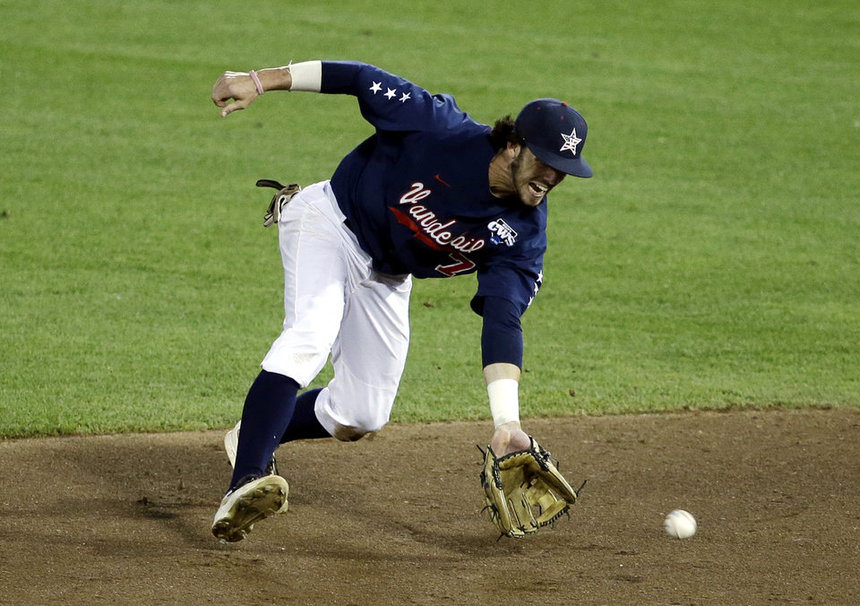 Photo - Vanderbilt second baseman Dansby Swanson handles a ground ball in the fifth inning of game one of the best-of-three NCAA baseball College World Series finals against Virginia in Omaha, Neb., Monday, June 23, 2014. (AP Photo/Nati Harnik)