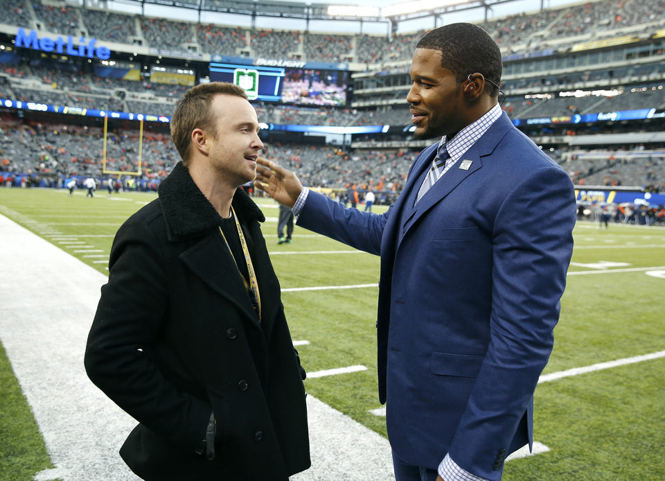 Photo - Actor Aaron Paul, left, talks to former NFL football player Michael Strahan before the NFL Super Bowl XLVIII football game between the Seattle Seahawks and the Denver Broncos, Sunday, Feb. 2, 2014, in East Rutherford, N.J. (AP Photo/Evan Vucci)