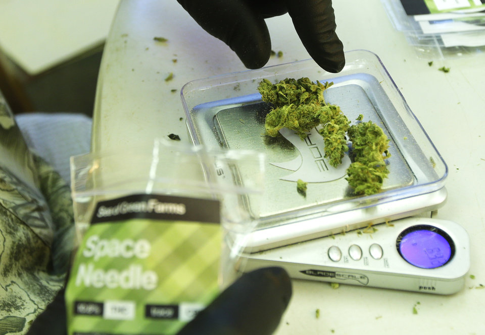 Photo - In this July 1, 2014, photo, a worker weighs out one-gram packets of a variety of recreational marijuana named
