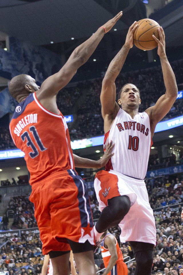 Photo - Toronto Raptors' DeMar DeRozan, right, shoots on Washington Wizards' Chris Singleton during first half NBA basketball action in Toronto, Thursday, Feb. 27, 2014. (AP Photo/The Canadian Press, Chris Young)