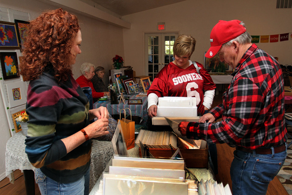 Photo - Sharon Rae Farris, left, shows her photography to Nancy and Larry Howard Saturday at the arts market in Norman.