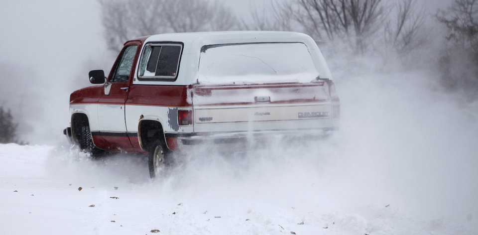 Photo - A 4 wheel drive vehicle drives through deep snow on E. Charter Oak Rd. in Logan County, Oklahoma February  1, 2011. Photo by Steve Gooch, The Oklahoman