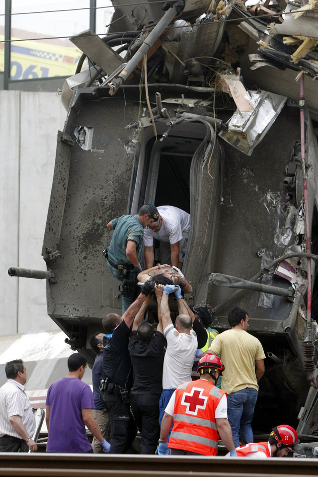 Photo - In this photo taken on Wednesday July 24 2013, A woman is evacuated from a train car at the site of a train accident in Santiago de Compostela, Spain. Spanish police on Friday detained the driver of a train that crashed in northwestern Spain, lowered the death toll from 80 to 78 and took possession of the
