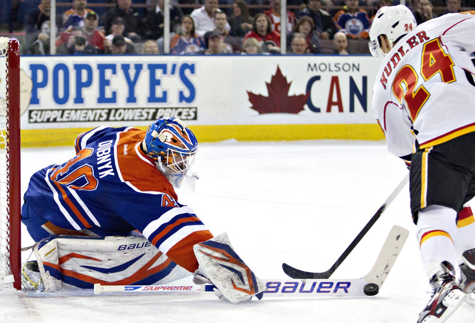 Photo - Calgary Flames Jiri Hudler (24) is stopped by Edmonton Oilers goalie Devan Dubnyk (40) during first period NHL hockey action in Edmonton, Alberta, on Monday April 1, 2013.  (AP Photo/The Canadian Press, Jason Franson)