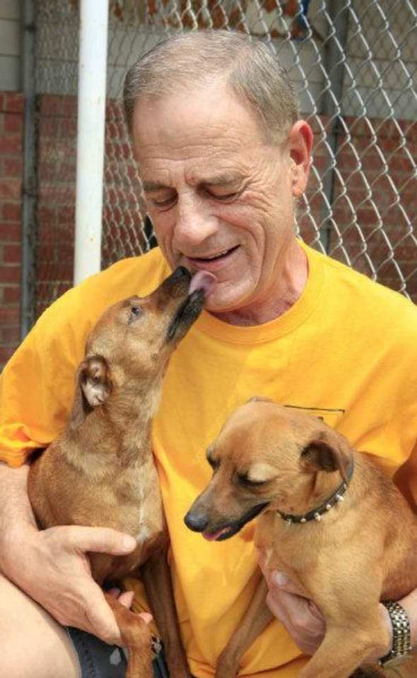 Photo - Ron Wingler, director of operations at Free to Live Animal Sanctuary, holds two rescued Italian greyhounds that are available for adoption. PHOTO BY PAUL B. SOUTHERLAND, THE OKLAHOMAN  PAUL B. SOUTHERLAND