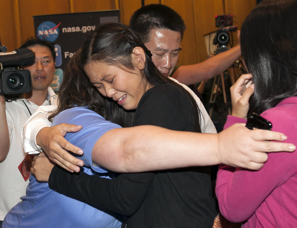 Clara Ma, winner of the Mars Science Laboratory naming contest for NASA's Mars rover Curiosity, third from left, hugs with NASA's friends and family members, as Curiosity lands safely into Mars surface after a complex new landing technique at NASA's Jet Propulsion Laboratory in Pasadena, Calif., Sunday, Aug. 5, 2012. (AP Photo/Damian Dovarganes)